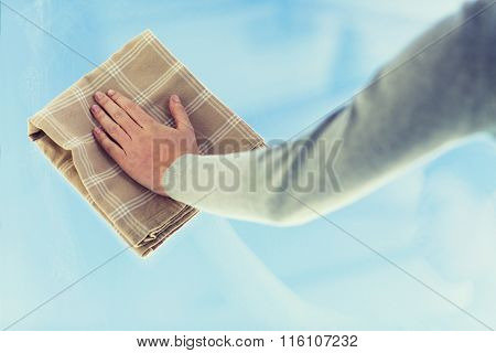 close up of woman hand cleaning window with cloth