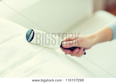 close up of woman hand with sticky roller cleaning