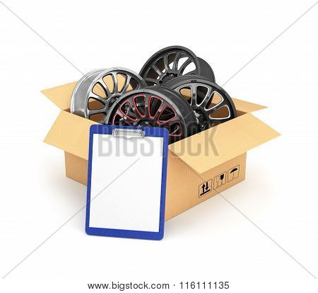 Automobile Rims In An Open Cardboard Box With A Folder For Documents