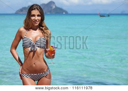 Sexy woman in bikini with cocktail on beach in Thailand