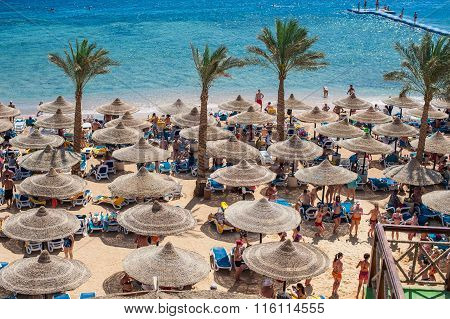 Sharm El Sheikh, Egypt, March 5, 2013: Beach with people under umbrellas and sea view Concorde El Sa