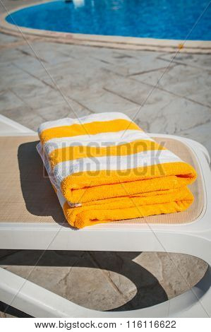 Yellow Towels On Sun Lounger Near The Swimming Pool