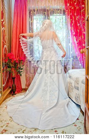 Bride In White Dress In The Room Looking Out The Window And Keeps Veil