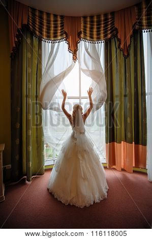 Bride In A White Dress In A Hotel Room Near The Window