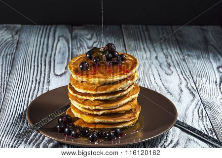 Stack of homemade pancakes with black currant and honey on brown plate on rustic background.
