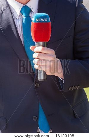 News Journalist With Microphone Reporting