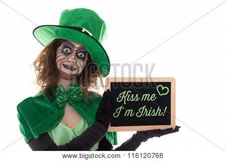 Green Leprechaun Holding A Slate With Text Kiss Me I´m Irish, Isolated On White