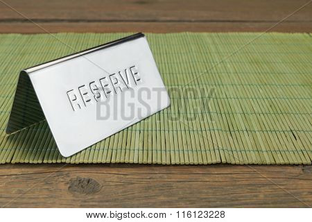 Metal Sign Reserve On The Restaurant Wood Table Background