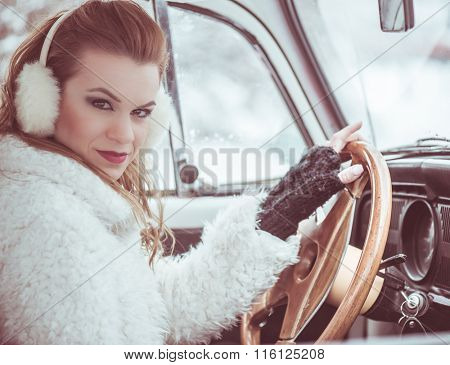 Driving a car at wintertime - pretty, young woman driving her vintage car at snowy road, color toned image