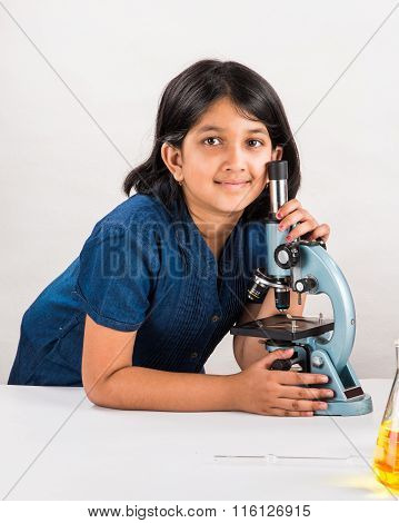 curious indian girl with microscope