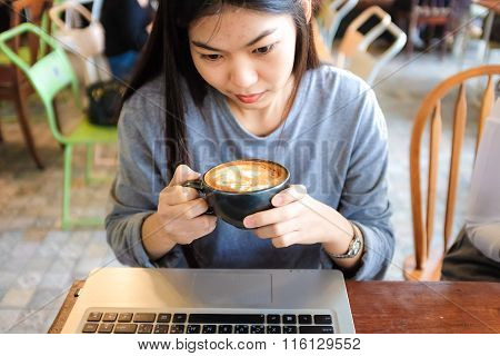 Beautiful Young Asian Woman With Coffee Using Laptop