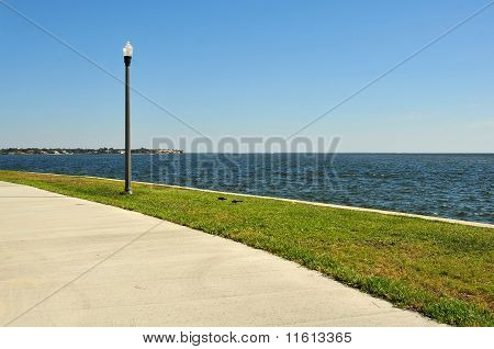 Sidewalk and lamppost near the water