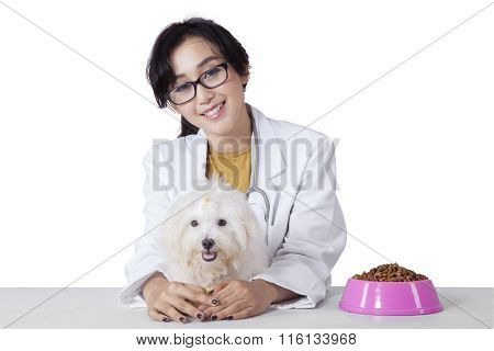 Young Veterinarian With Dog And The Dog Snack