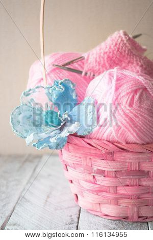 Vintage Knitting needles and yarn on wooden background in a basket