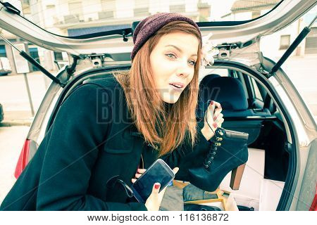 Cheerful Young Woman Showing High Heels Shoes  From The Trunk Of The Car -