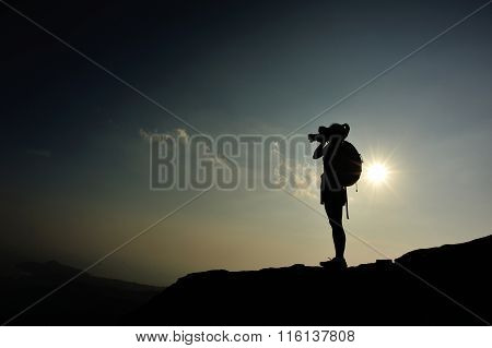 young woman backpacker taking photo on sunset mountain peak