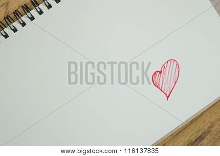 Red heard shape on notepad on wood desk