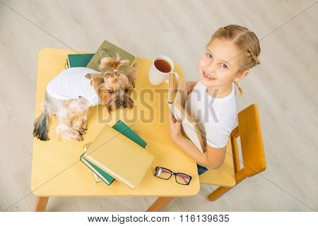 Little girl is studying with her dog.