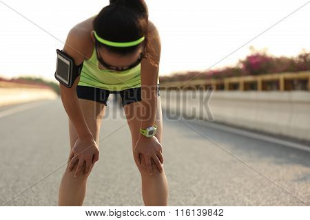 tired fitness young woman runner take a  rest after running hard on city road