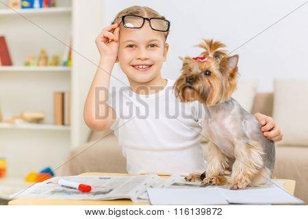 Little girl slightly hugging her dog.