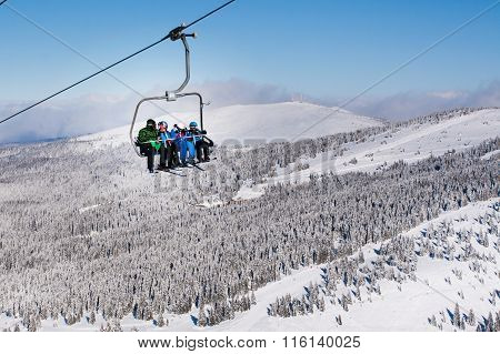 Skiers arriving to high mountain station on the ski lift