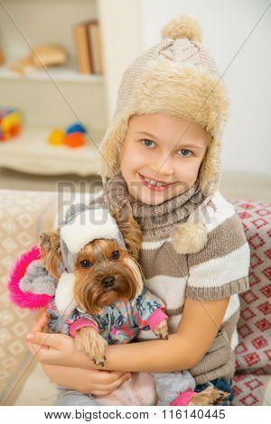 Little kid holding her pet Yorkshire.