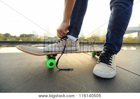closeup of skateboarder tying shoelace on city