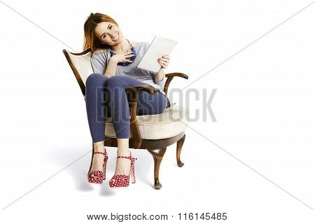 Woman Sitting On An Armchair With Tablet