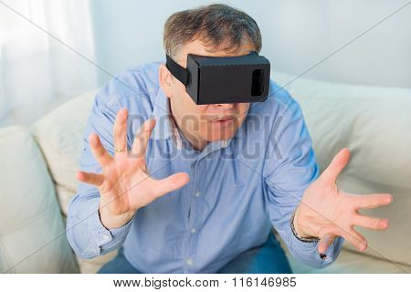 Man getting experience using VR-headset glasses of virtual reality at home much gesticulating hands