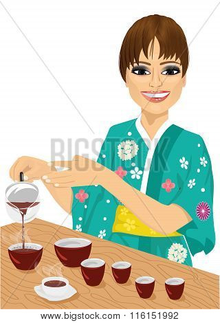 attractive woman in kimono pouring tea
