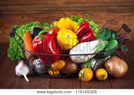 Fresh vegetables in basket on wooden board healthy eating
