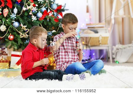 Two cute small brothers blows soap bubbles on Christmas tree background