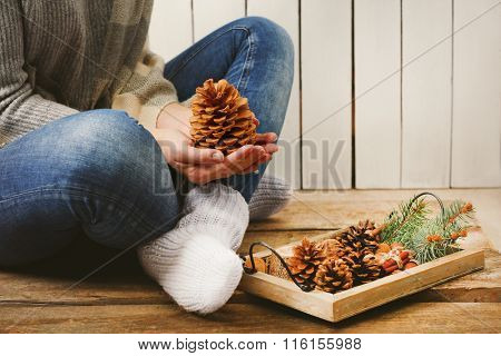 Woman holding pine cone and wooden basket with evergreen, closeup