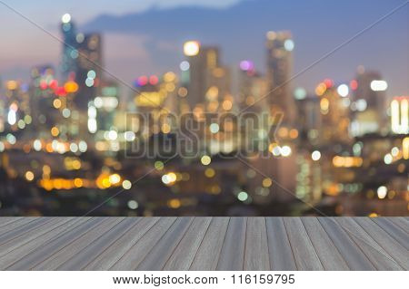 Opening wooden floor, blurred bokeh city light at night.