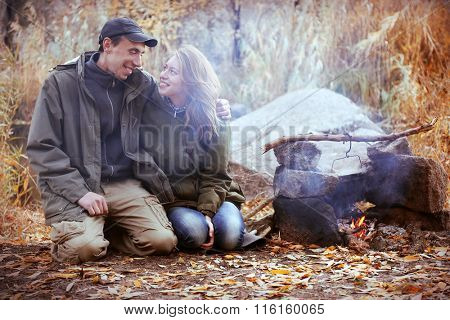 Couple sitting beside fireplace outdoors
