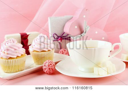 Tasty cupcakes with gifts and decorations on pink background