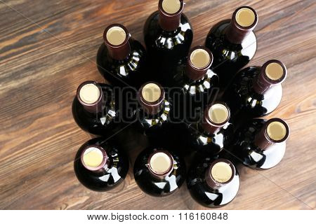 Stacks of wine bottles on wooden background, upside view.