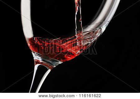 Pouring red wine on dark background