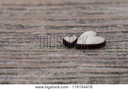 wooden hearts placed nicely on vintage wood background