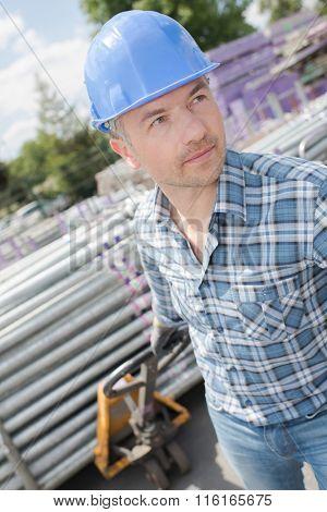 Worker pulling pallet of tubing