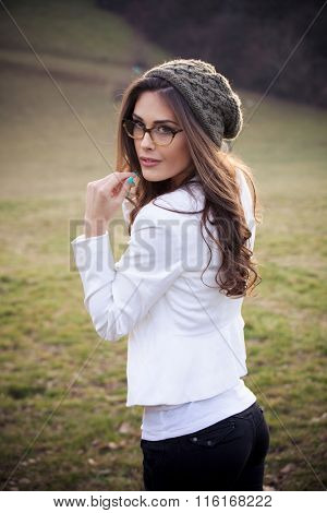 young woman with eyeglasses and wooll cap portrait, outdoor on field winter day