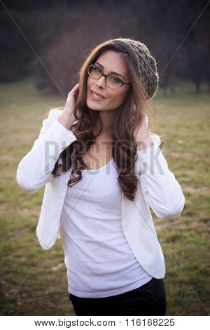 young woman with eyeglasses and wooll cap portrait, outdoor winter day, closeup
