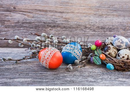 Easter Eggs Decorated With Lace, Pussy-willow  And Quail Eggs In Small Nest On Wooden Background.