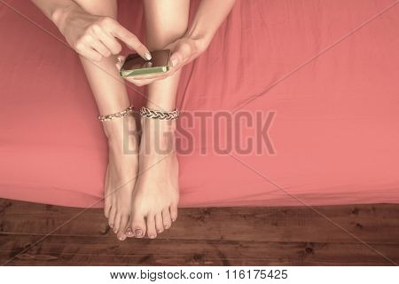Girl typing messages in the bed.