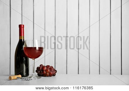 Red wine with grape on wooden wall background