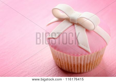 Tasty cupcake with bow on color wooden background