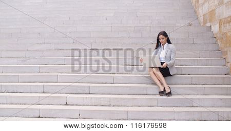 Pretty young worker sitting on steps with laptop