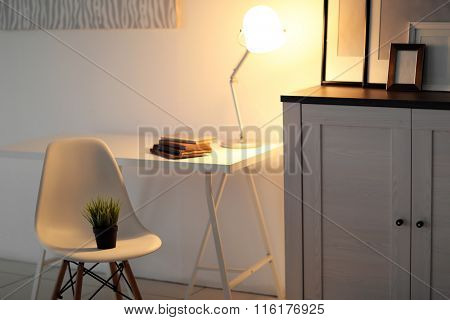 Room interior with commode with chair, plant, lamp and table on white wall background