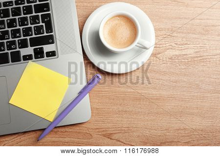 Empty yellow adhesive paper on laptop keyboard, pen and coffee cup on desk background