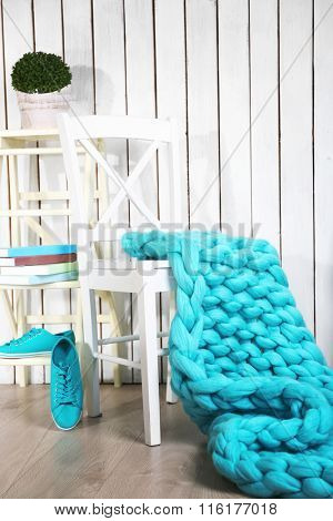 Knitted woolen blanket on stairs, on home interior background